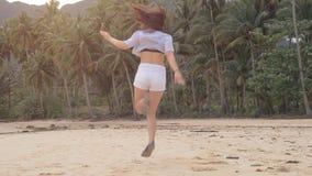 De gelukkige looppas van het reizigersmeisje op leeg strand in mooie roze zonsondergang, springt en lacht hoogtepunt van geluk, r stock footage