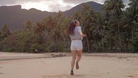 De gelukkige looppas van het reizigersmeisje op leeg strand in mooie roze zonsondergang, springt en lacht hoogtepunt van geluk, r stock video