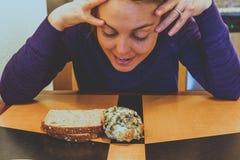 De gelukkige maar toch onbesliste jonge volwassen vrouw beslist tussen een bosbessenscone of een stuk van toost voor ontbijt, ter royalty-vrije stock afbeelding