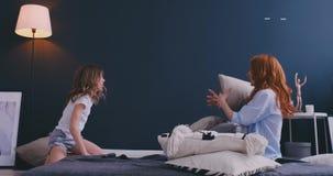 De gelukkige mamma oudere zuster en het kindmeisje genieten van grappige hoofdkussenstrijd op bed, babysittermoeder met weinig jo stock footage