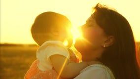 De gelukkige mammaspelen met kind, moeder werpt kind in lucht in heldere stralen van de zon Langzaam het schieten close-up stock video