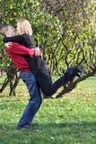 De gelukkige man omhelst en heft vrouw in park op Royalty-vrije Stock Foto's