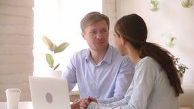 De gelukkige medewerkers die samen het spreken werken genieten van groepswerk met laptop stock videobeelden