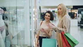 De gelukkige meisjes babbelen in winkelcomplex besprekend nieuwe inzameling die van ondergoed op kleding op ledenpoppen richten stock video