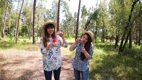 De gelukkige meisjes glimlachen en de slagenzeepbels in park in de zomer, pret en geluk stock video