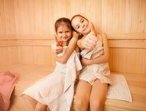 De gelukkige meisjes in sauna het tonen beduimelt omhoog stock afbeelding