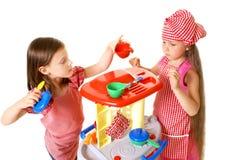 De gelukkige meisjes spelen het koken Stock Foto's