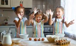 De gelukkige meisjes van zusterskinderen bakken koekjes, kneden deeg, spelen verstand Royalty-vrije Stock Afbeelding