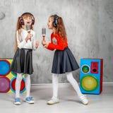 De gelukkige meisjes zingen en luisteren aan muziek in hoofdtelefoons Het bureau van C stock foto's
