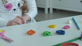 De gelukkige meisjespelen met gekleurde plasticine, rolt ballen, zijn de handen op de Desktop cijfers en kleurpotloden, stock videobeelden