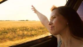 De gelukkige meisjesritten in de auto, trekt haar uitdeelt venster en lacht het golven van zijn hand van autoraam op een hete de  stock footage