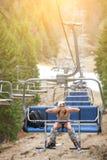 De gelukkige meisjesskiër zit bij de skilift en berijdt tot de bovenkant van de berg Royalty-vrije Stock Afbeeldingen