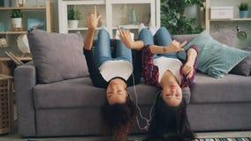 De gelukkige meisjesvrienden luisteren aan muziek gebruikend smartphone met oortelefoons en het dansen het liggen ondersteboven o stock videobeelden