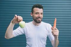 De gelukkige mens bevindt zich en houdt fruit en groente in handen Het is groene appel en oranje wortel Hij kijkt  royalty-vrije stock foto's