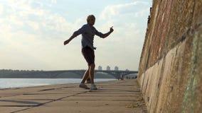 De gelukkige Mens danst Disco op een Riverbank met een Hoge Steenmuur in de Zomer stock video