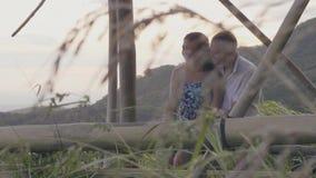 De gelukkige mens die jong meisje op groen heuvelslandschap koesteren omvatte tropisch bos Romantisch en paar die omhelzen geniet stock footage