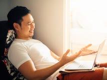 De gelukkige mens gebruikt laptop en ontspant op bank in de ochtend stock afbeelding