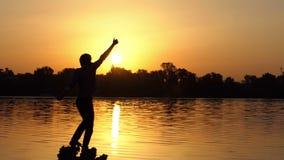 De gelukkige mens heft omhoog een duim op een meerbank bij zonsondergang in slo-mo op stock videobeelden