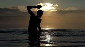 De gelukkige mens heft stromen omhoog van water in een meer bij zonsondergang in slo-mo op stock video