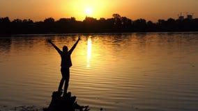 De gelukkige mens heft twee handen op een meerbank bij zonsondergang in slo-mo op stock footage