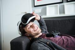 De gelukkige mens ligt op bank die virtuele werkelijkheidsglazen dragen Stock Foto
