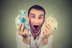 De gelukkige mens met extatische geld euro bankbiljetten viert succes stock afbeelding