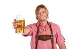 De gelukkige mens met leerbroeken houdt bierstenen bierkroes Stock Afbeelding