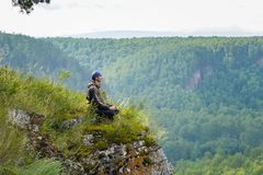 De gelukkige mens met ogen gesloten zitting op de rand van een klip die in yoga mediteren stelt, ontspant en vrije tijd in harmon stock afbeelding
