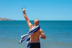 De gelukkige mens op het strand geniet van de vrijheid van het concept rust en vakantie royalty-vrije stock afbeelding