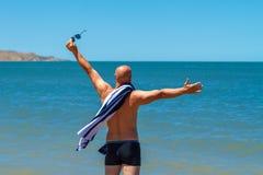 De gelukkige mens op het strand geniet van de vrijheid van het concept rust en vakantie royalty-vrije stock afbeeldingen