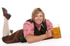 De gelukkige mens op vloer houdt meest oktoberfest bierstenen bierkroes Royalty-vrije Stock Afbeelding