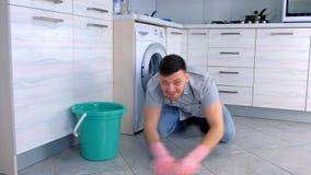 De gelukkige mens in rubberhandschoenen wast en oneffenheden hard de vloer in de keuken die, die op de vloer zitten en camera bek stock footage