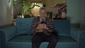De gelukkige mens speelt spel op zijn mobiele telefoonzitting op de bank 4K stock footage