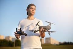 De gelukkige mens toont u kleine compacte hommel en ver controlemechanisme Proef houdt quadcopter en RC in zijn handen royalty-vrije stock fotografie