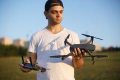 De gelukkige mens toont u kleine compacte hommel en ver controlemechanisme Proef houdt quadcopter en RC in zijn handen stock foto's
