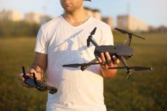 De gelukkige mens toont u kleine compacte hommel en ver controlemechanisme Proef houdt quadcopter en RC in zijn handen Geen gezic stock afbeelding