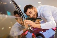 De gelukkige mens wat betreft auto in auto toont of salon Stock Fotografie