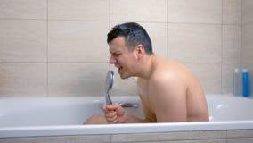 De gelukkige mens zingt terwijl hij in badkuip wast stock videobeelden