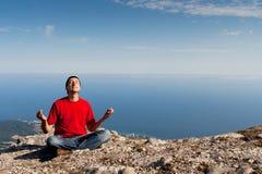 De gelukkige mens zit yoga stelt op de berg royalty-vrije stock foto