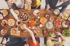 De gelukkige mensen eten gezonde maaltijd bij de gediende partij van het lijstdiner Stock Afbeeldingen