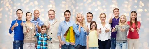 De gelukkige mensen met het winkelen zakken het tonen beduimelen omhoog Royalty-vrije Stock Afbeelding