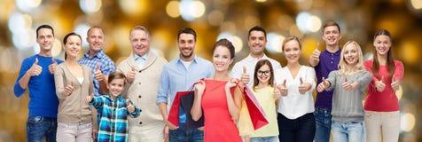 De gelukkige mensen met het winkelen zakken het tonen beduimelen omhoog Stock Foto's
