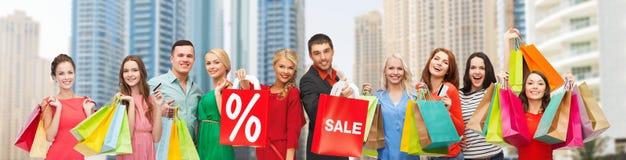De gelukkige mensen met verkoop ondertekenen het tonen van duimen Royalty-vrije Stock Foto