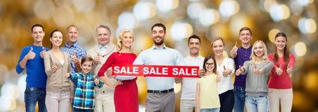 De gelukkige mensen met verkoop ondertekenen het tonen van duimen Stock Afbeelding