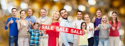 De gelukkige mensen met verkoop ondertekenen het tonen van duimen Royalty-vrije Stock Foto's