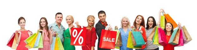 De gelukkige mensen met verkoop ondertekenen op het winkelen zakken Royalty-vrije Stock Foto's