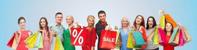 De gelukkige mensen met verkoop ondertekenen op het winkelen zakken Stock Foto's