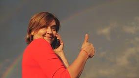 De gelukkige midden oude vrouw toont duim en spreekt met telefoon in langzame motie stock footage
