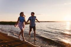De gelukkige minnaars lopen op het strand stock afbeeldingen
