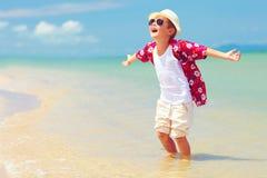 De gelukkige modieuze jong geitjejongen geniet van het leven op de zomerstrand Stock Fotografie